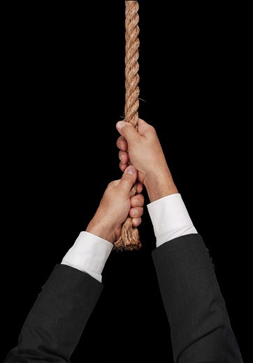 A man Hanging at the End of a rope on black : Stock Photo