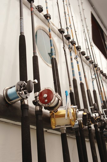 Deep Sea fishing poles lined up on the side of a sport fishing boat : Stock Photo