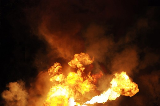 erupting gasoline fire shot at night from a distance of 200 meters : Stock Photo