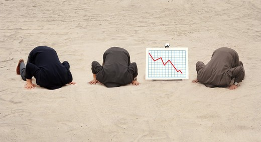 Three businessmen with their heads in the sand, kneeling next to a graph showing lost revenue : Stock Photo