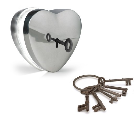 key unlocking a metal heart : Stock Photo