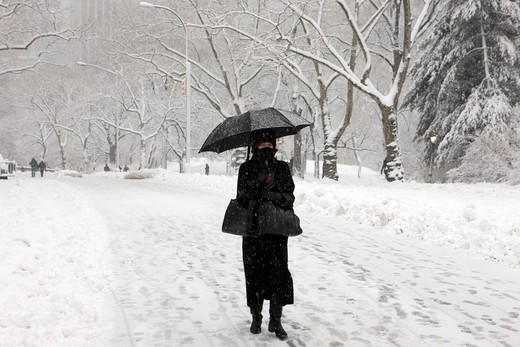 Woman walking in snow with an umbrella, New York City, New York State, USA : Stock Photo