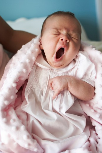 Stock Photo: 4196-101 Tired baby yawning in mother's arms