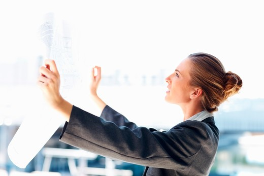 Stock Photo: 4197R-15093 Young successful business woman holding a blueprint, studying it