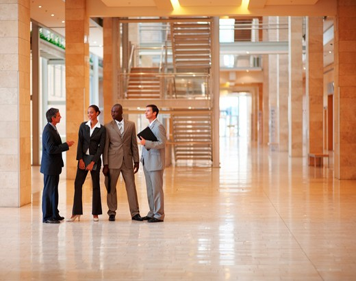 Stock Photo: 4197R-15208 Group of successful business colleagues standing at a hallway