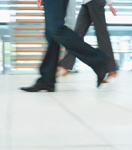 Low section motion image of business people walking at the office : Stock Photo