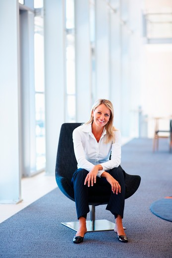 Stock Photo: 4197R-16616 Relaxed young business woman sitting on a chair at a hallway