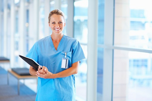 Stock Photo: 4197R-16743 A happy smiling nurse standing in blue uniform holding a file