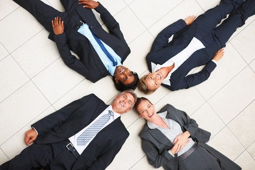 Stock Photo: 4197R-17662 A Happy team of business colleagues lying in a circle