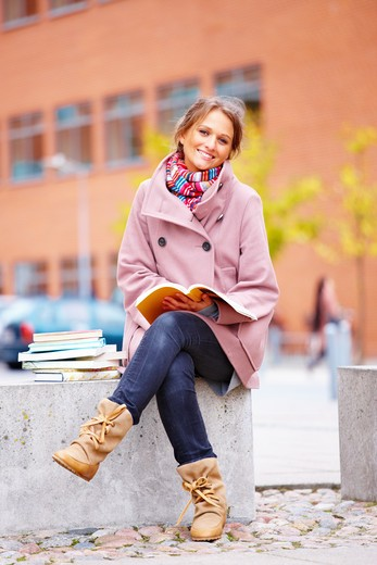 Young happy woman sitting with books in campus : Stock Photo