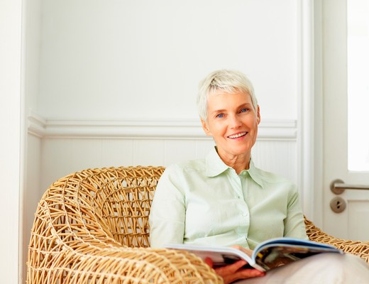 Senior woman sitting on a chair while reading a book : Stock Photo