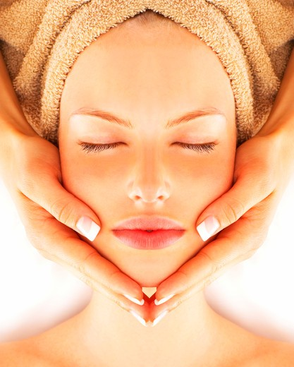 Beautiful young woman receiving facial massage : Stock Photo