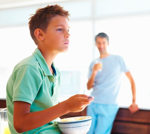 Young boy lost in thoughts, having breakfast with his dad in the background : Stock Photo