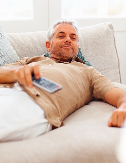 A retired aged man spending time by watching television : Stock Photo