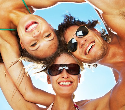 Group of happy young people in circle at beach : Stock Photo