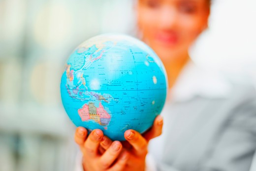 Stock Photo: 4197R-25249 Business woman holding a globe in the hand, focus on globe