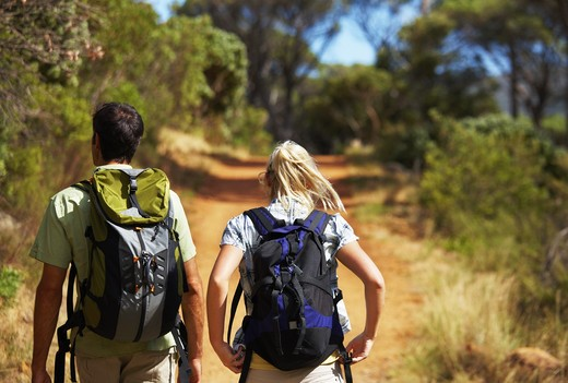 Stock Photo: 4197R-27249 Rear view of a young couple carrying backpacks and walking through a forest