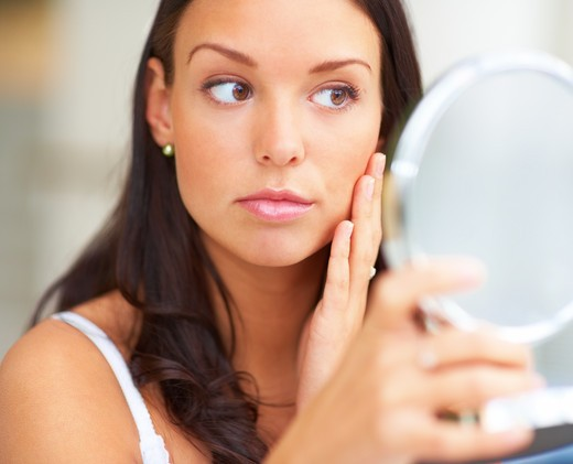 Stock Photo: 4197R-27571 Closeup portrait of young woman holding a mirror