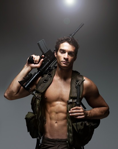 Stock Photo: 4197R-49199 Attractive soldier looking at the camera while holding his M16 rifle over his shoulder