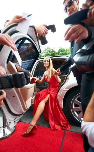 Stock Photo: 4197R-49411 Paparazzi-view of a gorgeous young starlet emerging from a white limousine onto the red carpet