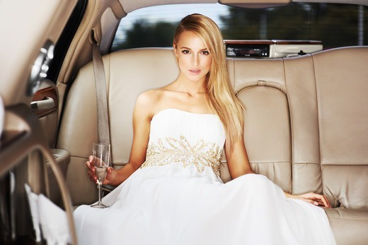 Portrait of a high society young beauty holding champagne in the back of a limousine : Stock Photo