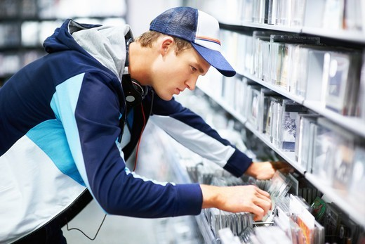 Stock Photo: 4197R-49515 A trendy young guy flipping through the selections on the rack at his favourite music store