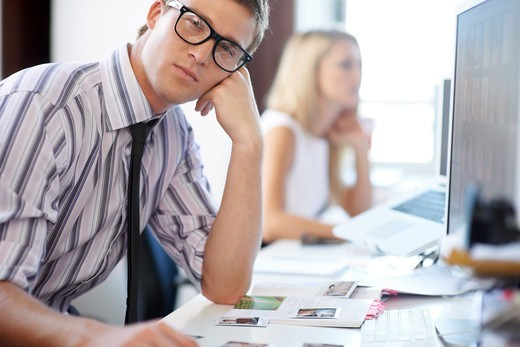 Portrait of a hipster young male sitting at his office desk-copyspace : Stock Photo
