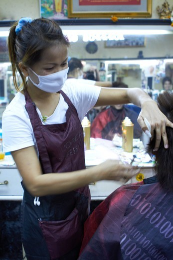 Stock Photo: 4197R-50334 Female Thai hairdresser wearing a surgical mask while cutting hair