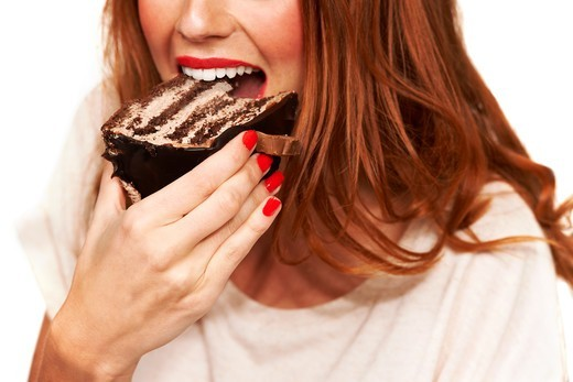 Cropped closeup of a young woman taking a bite from a piece of cake : Stock Photo