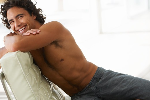 Stock Photo: 4197R-50911 Gorgeous young man smiling at you without a shirt while reclining on  a modern sofa