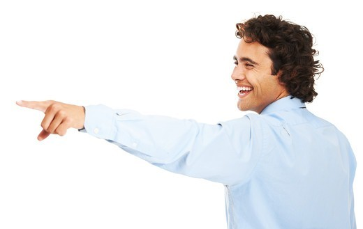 A young businessman pointing at something and laughing : Stock Photo