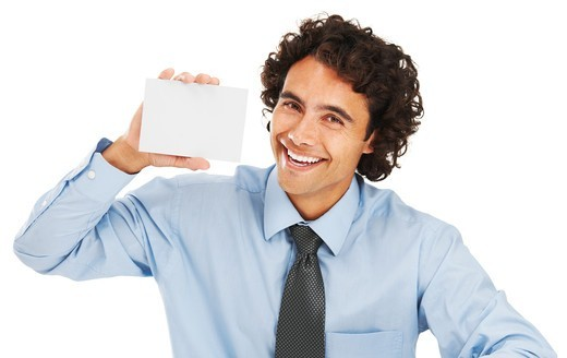 Portrait of a young businessman holding a blank card : Stock Photo