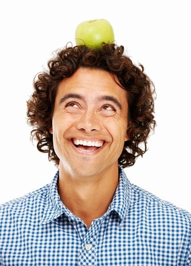 Handsome young man balancing an apple on his head - Isolated on white : Stock Photo