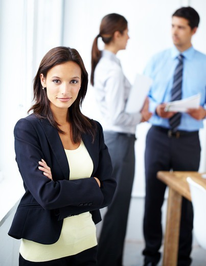 Young businesswoman standing with her arms folded and looking at the camera with two co-workers in the background : Stock Photo