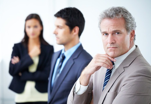 Stock Photo: 4197R-51371 Serious businessman looking at the camera with two co-workers standing in the background