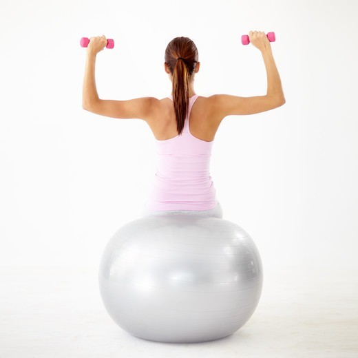 Rear view of a young woman pressing dumbbells while sitting on a gym ball - Isolated on white : Stock Photo
