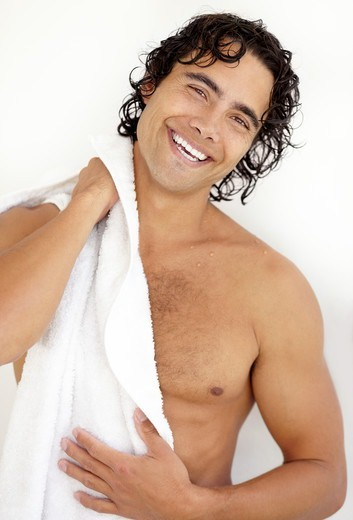 Portrait of a sexy young man drying himself after a refreshing shower : Stock Photo