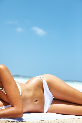 Stock Photo: 4197R-52312 Portrait of woman with sexy figure relaxing in bikini on beach