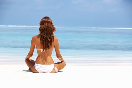 Portrait of young woman meditating in lotus position at beach : Stock Photo