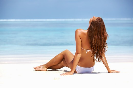 Rear view of young woman relaxing at beach : Stock Photo