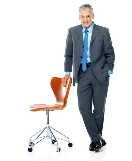 Stock Photo: 4197R-52505 Portrait of senior male executive standing with a chair on white background