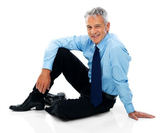 Stock Photo: 4197R-52623 Relaxed mature business man sitting on the floor isolated over white background