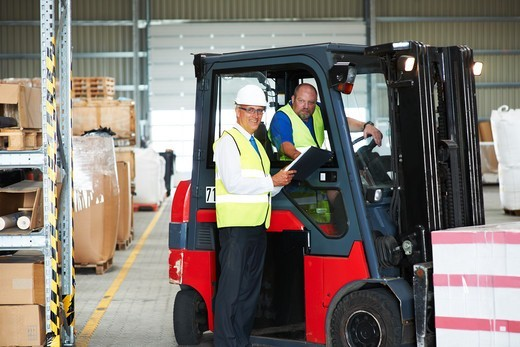 Stock Photo: 4197R-52669 Warehouse foreman smiling alongside an employee on a forklift