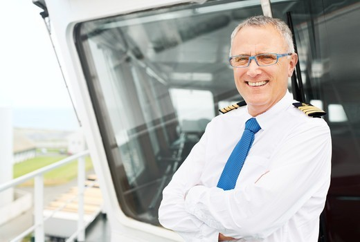 Portait of ship captain smiling and crossing his arms outside of the deckhouse : Stock Photo