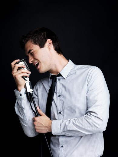 Stock Photo: 4197R-5283 Portrait of a successful young male star performer singing with old fashioned microphone against black background