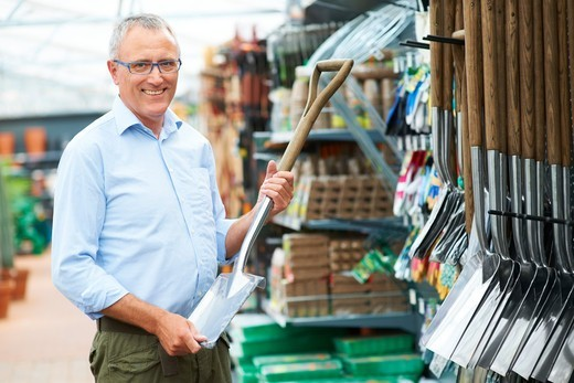 Mature caucasian man standing and holding spade looking and smiling : Stock Photo