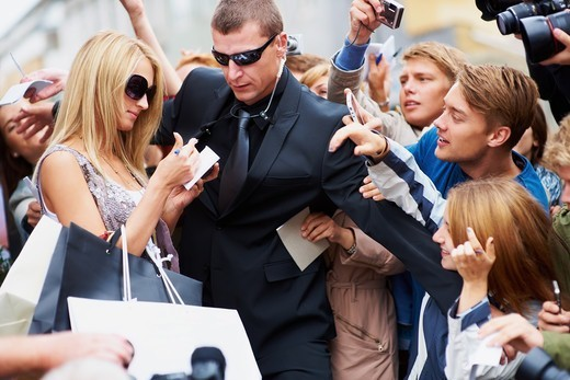 Pretty young star signing autographs while her bodyguard holds back the public : Stock Photo
