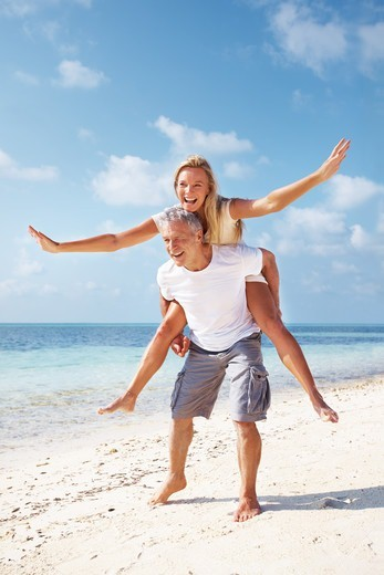 Stock Photo: 4197R-53304 Full length of happy mature couple having piggyback ride on beach