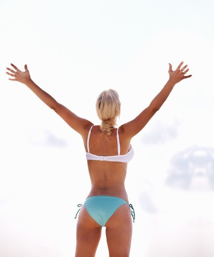 Stock Photo: 4197R-53378 Rear view of fit woman standing with hands raised on the beach