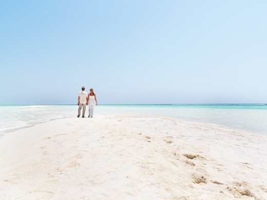 Stock Photo: 4197R-53435 Image of mature couple taking a walking a by the sea - Copyspace